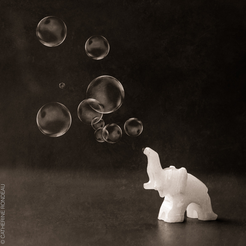 Elephant figurine blowing soap bubbles.