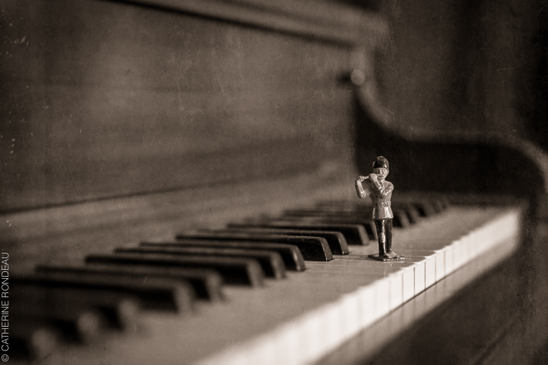 Soldier figurine playing the flute on piano keys.