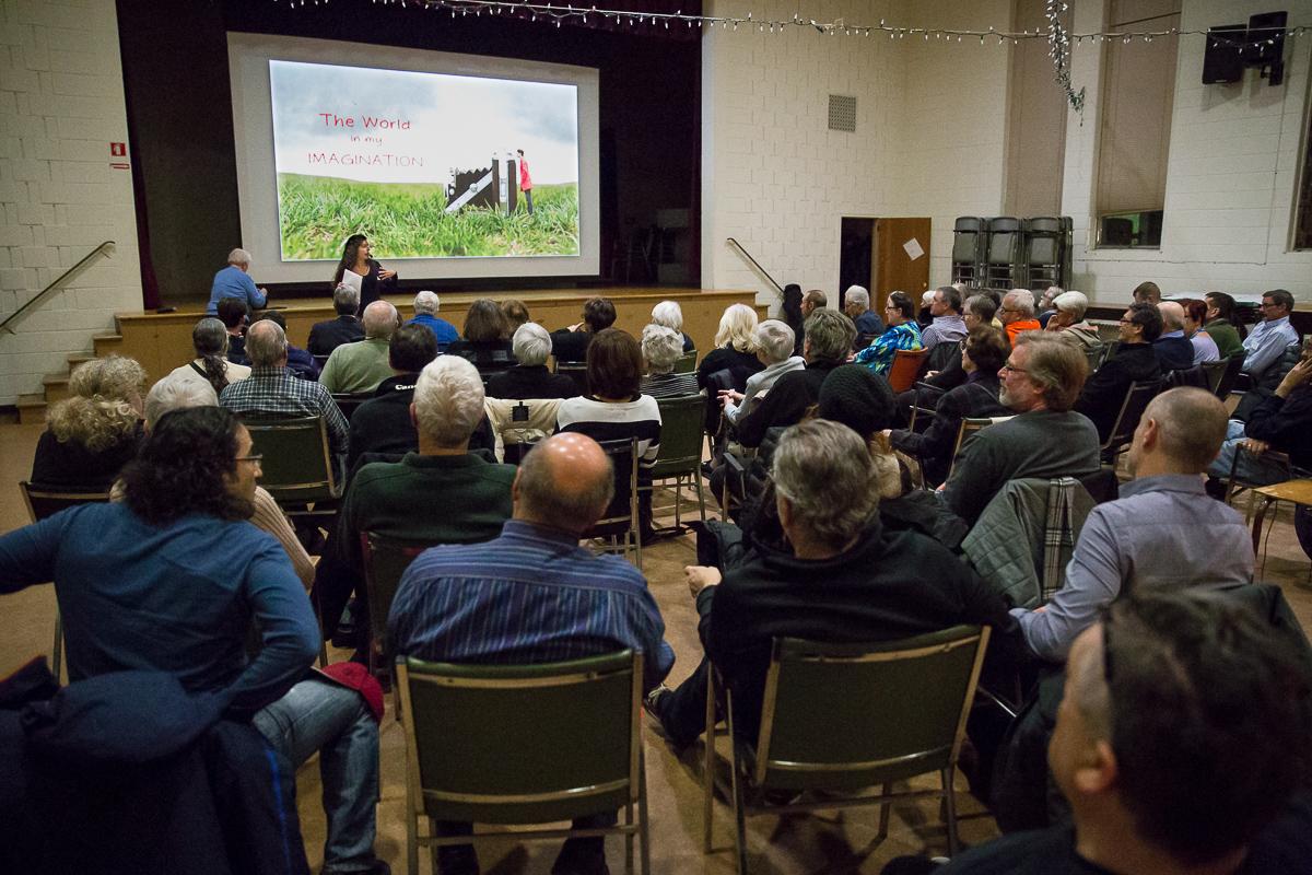 Vue de l'arrière d'une salle remplie de personnes assises qui regardent une conférencière sous une photo projetée sur un écran.