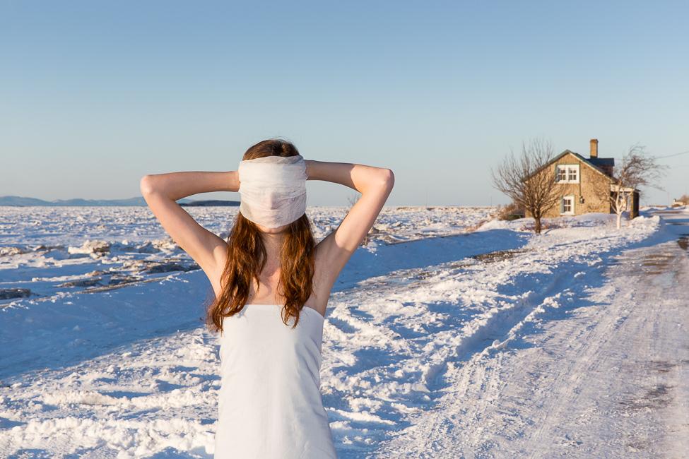Une jeune fille vêtue d'un drap blanc enveloppe son visage dans un tissu blanche, elle se tient dans un décor hivernal, sur le bord du fleuve, une maison à l'arrière-plan.