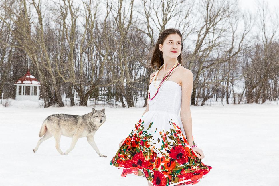 Adolescente dans une robe d'été fleurie dans un paysage de neige avec une forêt et un loup en arrière-plan.