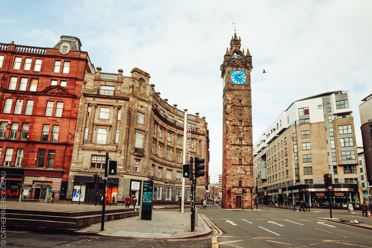 Street intersection dominated by tall clock tower.