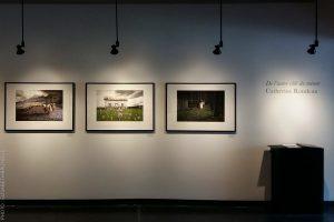 Vue d'une salle d'exposition avec trois cadres de photographies accrochés au mur.