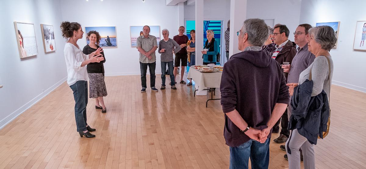 Des gens se tiennent debout dans une salle d'exposition et semble écouter une femme parler à l'avant