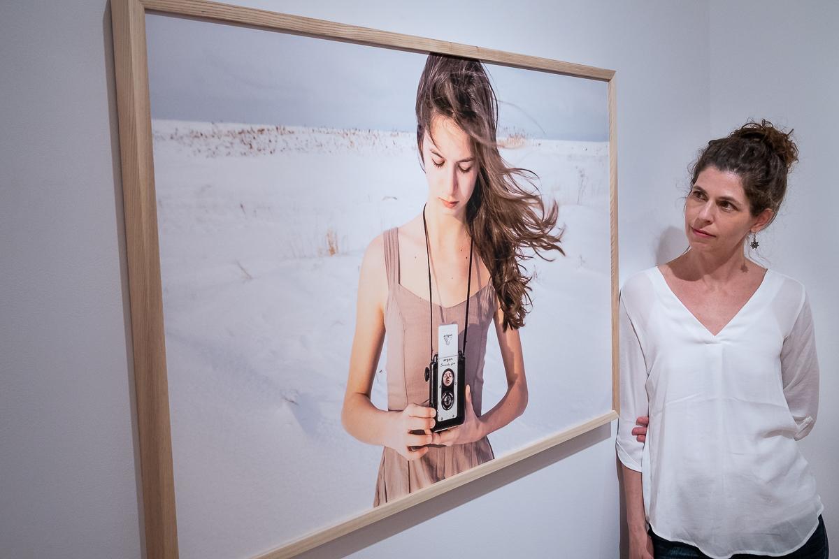 Une femme regarde une grande photographie encadrée d'une jeune fille qui tient un vieil appareil photo dans la neige.