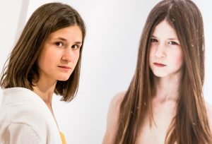teenage photo model Emma Boudou takes the pose next to a large scale framed portrait of herself