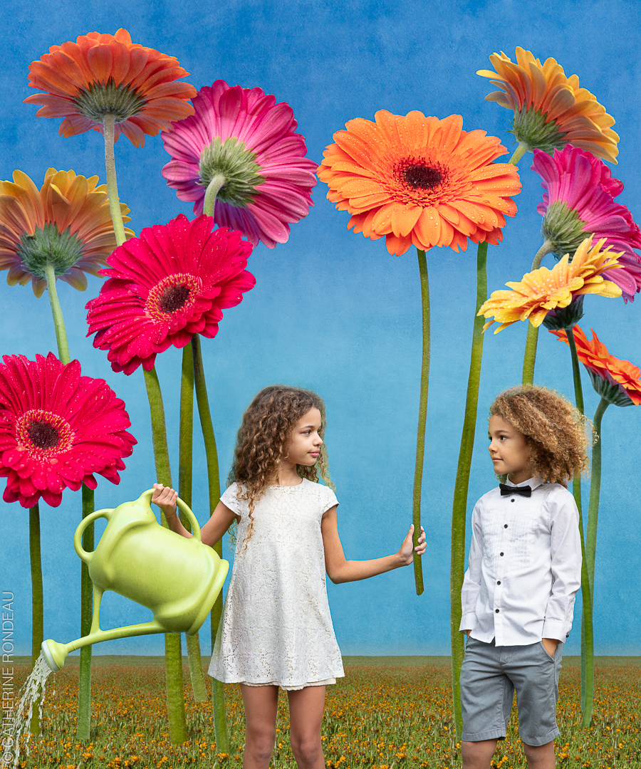 Two children stand beneath giant flowers