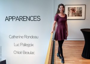 artist Catherine Rondeau stands in front of her photograph at an opening reception