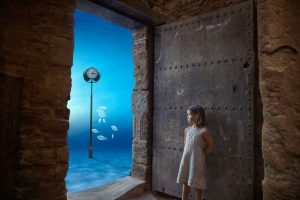 surreal tableau with little girl looking at fish swimming underwater through a door