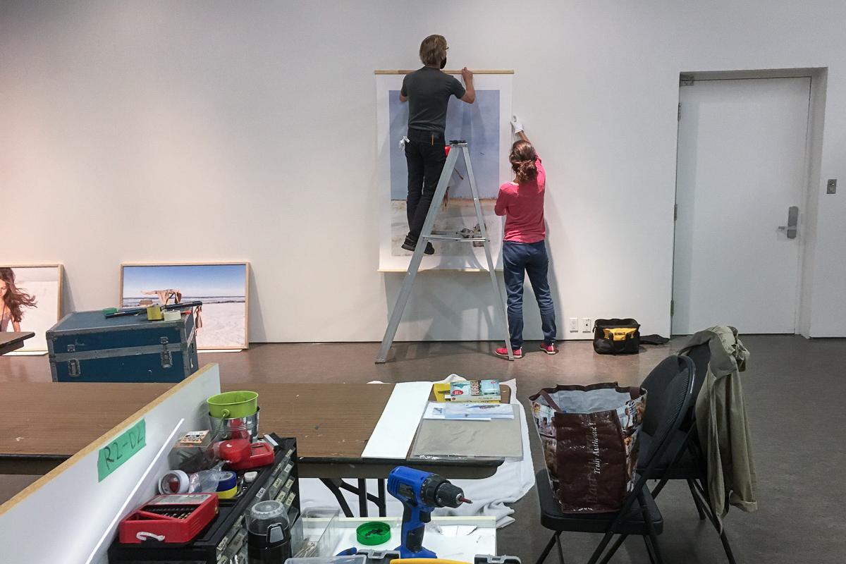Deux personnes de dos accrochent une oeuvre d'art au mur dans une salle d'exposition
