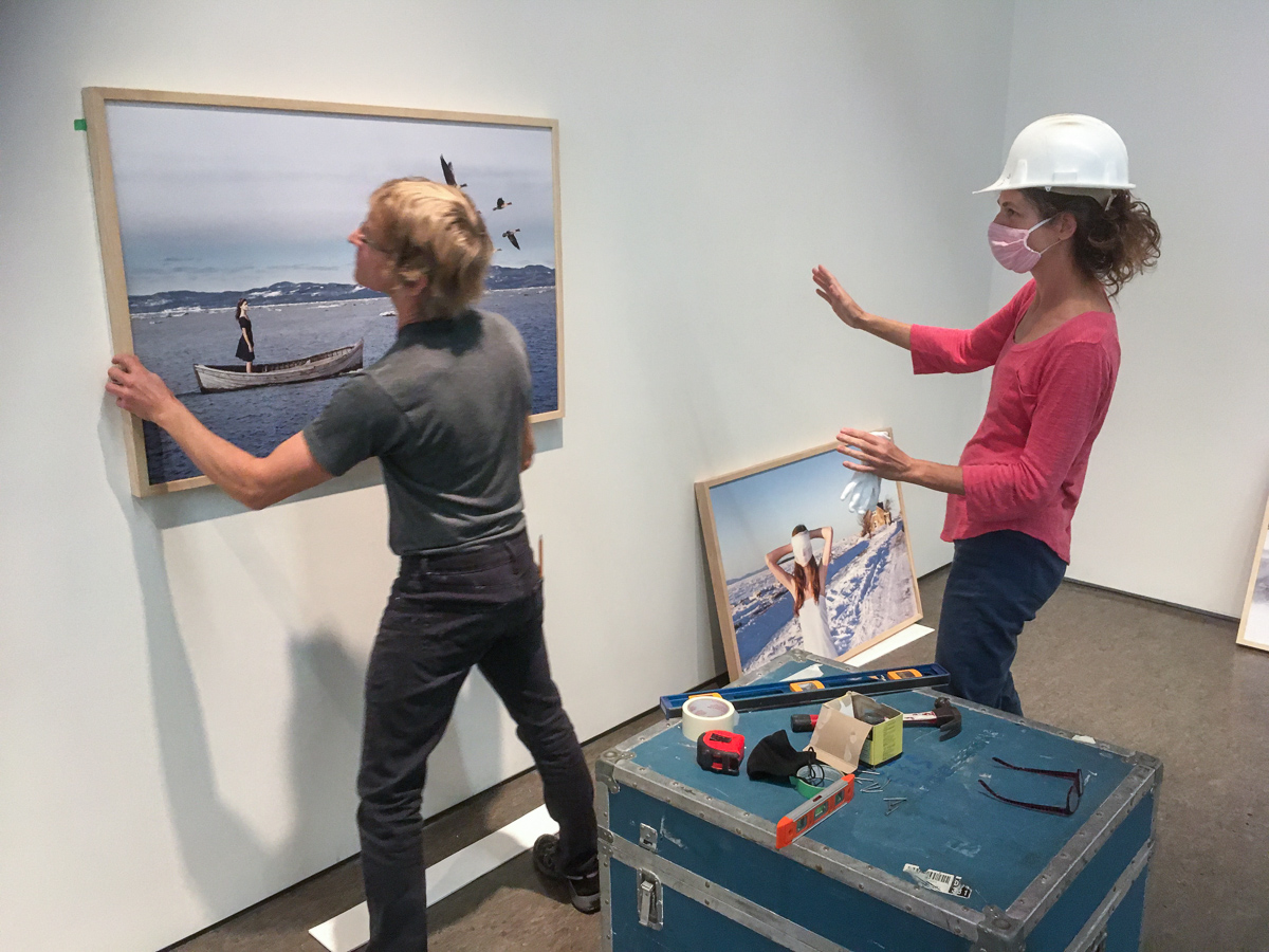 A man hangs a work of art on the wall under the supervision of a woman wearing a construction helmet
