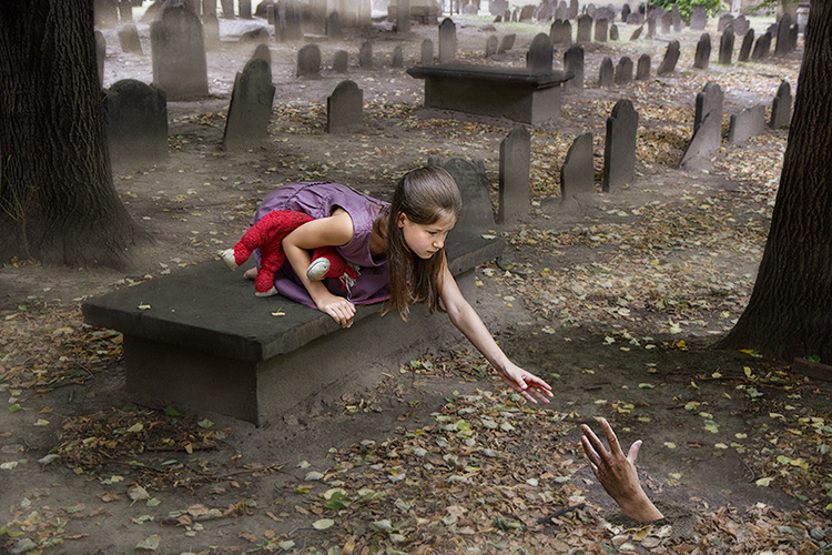 Photo of a child reaching out to a hand in a cemetery