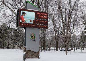 Illuminated sign in a park announcing the photo exhibit Traversée boréale in Dorval
