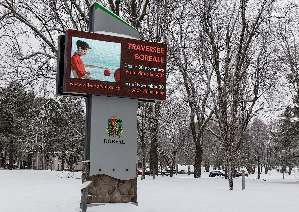 Illuminated sign in a park announcing the photo exhibit Traversée boréale in Dorval