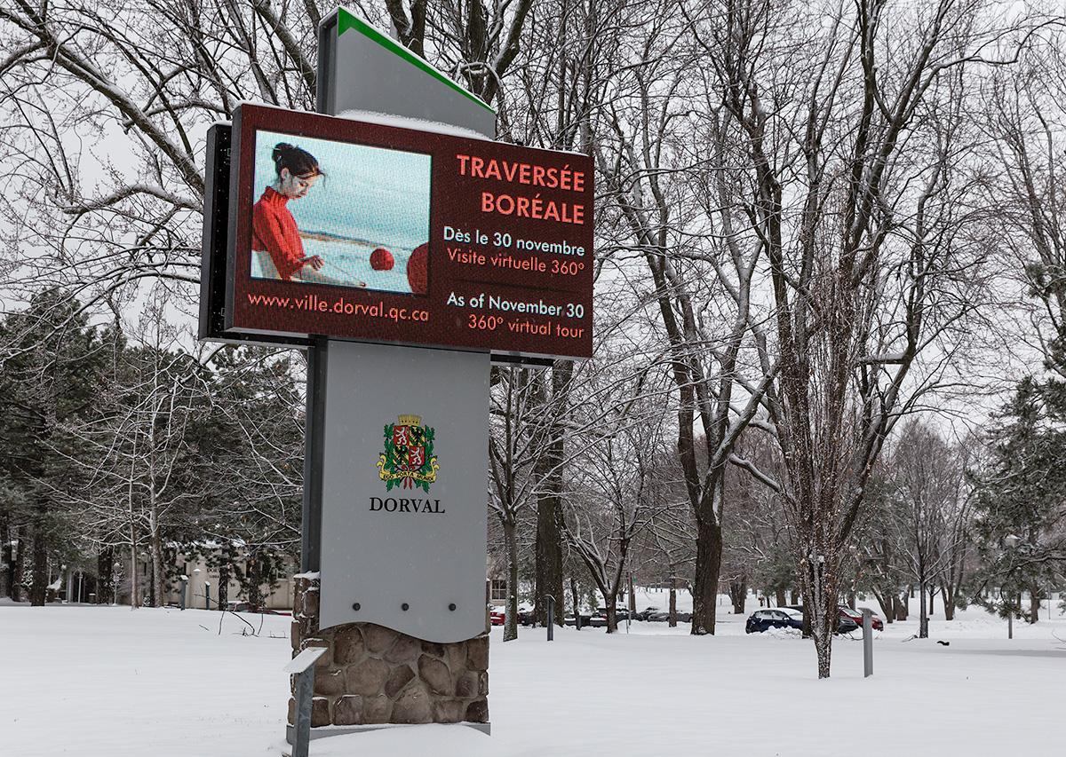 Panneau lumineux dans un parc enneigé indiquant la tenue de l'exposition Traversée boréale à Dorval