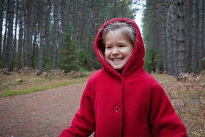Enfant vêtue d'un manteau rouge rit avec la forêt derrière elle