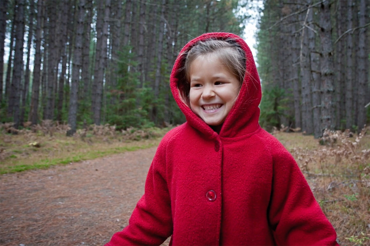 Photo of a child dressed in a red hooded coat with the forest behind her