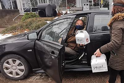 Photo d'un homme qui ouvre la portière d'une auto en tenant une boîte trio culturel du CNE