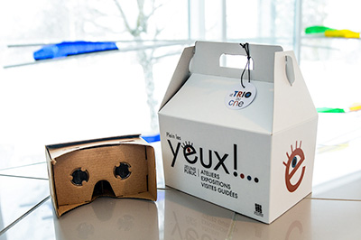 photo of a virtual reality helmet and a box showing PLEIN LES YEUX, CNE