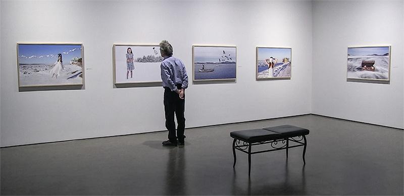 dans une salle d'exposition un homme de dos regarde une des photographies accrochées au mur